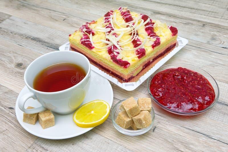 Kopp med te-, kaka- och hallondriftstopp på en trätabell royaltyfri bild