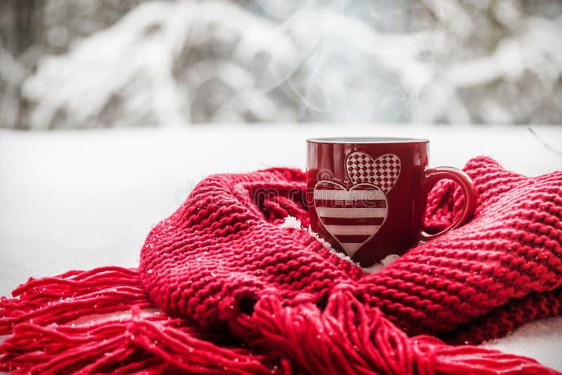 Kopp med två hjärtor och en varm drink som slås in i en halsduk i snön royaltyfria bilder