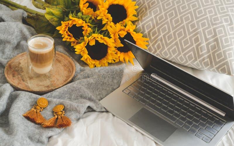 Kopp med varm cappuccino, grå pastellfärgad woolen filt, solrosor, sovrum arkivbild