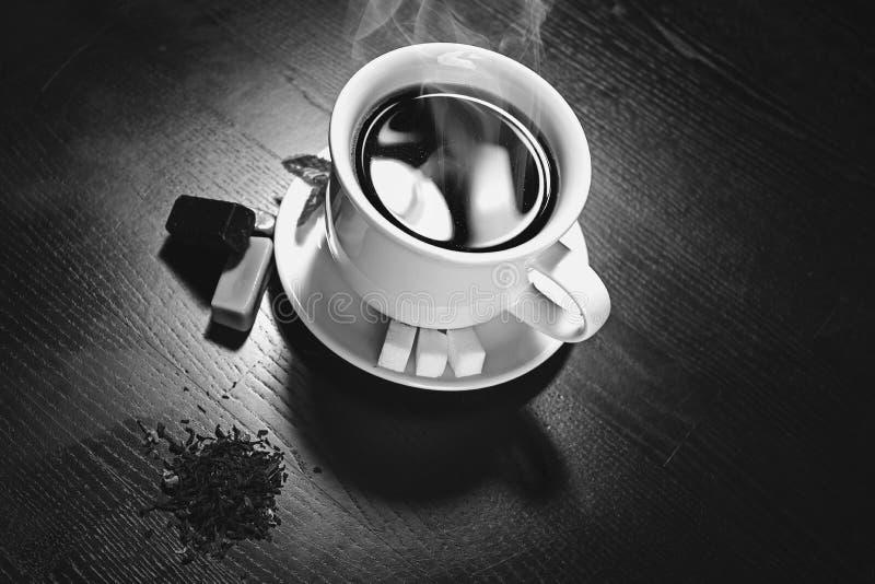 kopp med varm flytande och ånga på svart royaltyfria bilder