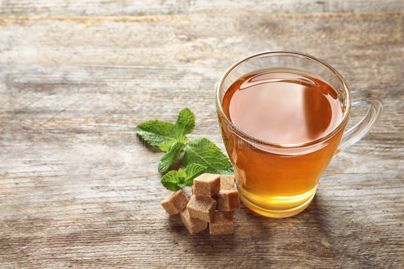 Kopp med varmt aromatiskt mintkaramellte på trätabellen arkivfoton