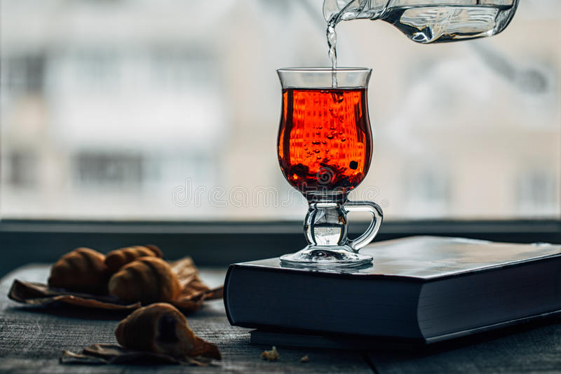 Kopp med varmt te på en frostig bakgrund för fönster för vinterdag arkivfoto