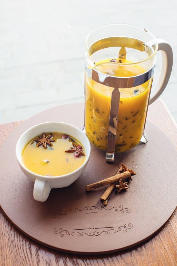 Kopp- och exponeringsglastekanna med kryddigt fruktte med apelsinen arkivbilder