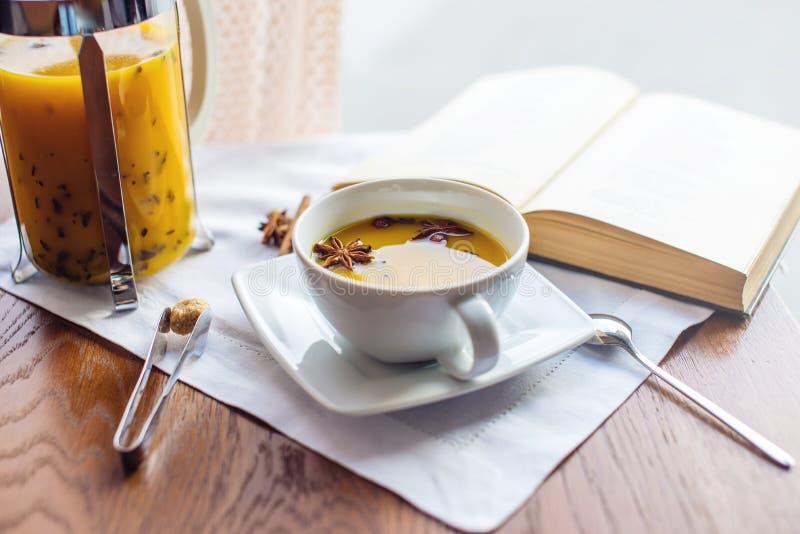 Kopp- och exponeringsglastekanna med kryddigt fruktte med apelsinen royaltyfri fotografi
