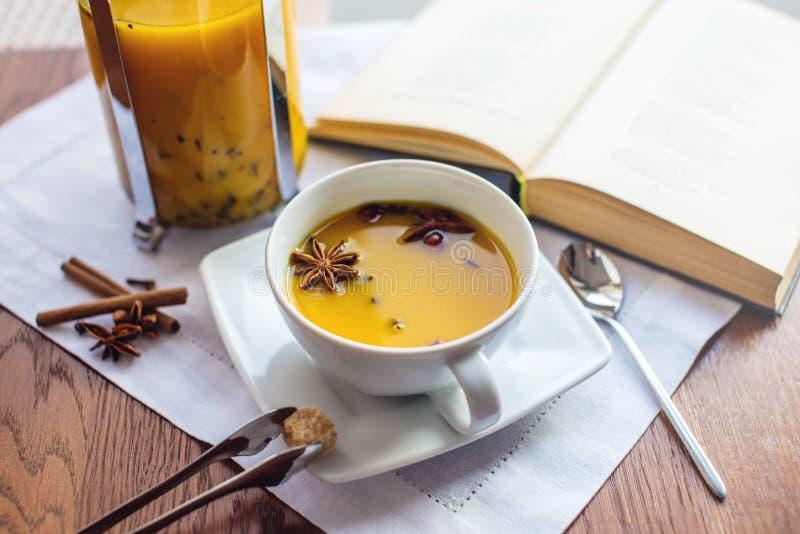 Kopp- och exponeringsglastekanna med kryddigt fruktte med apelsinen royaltyfri bild