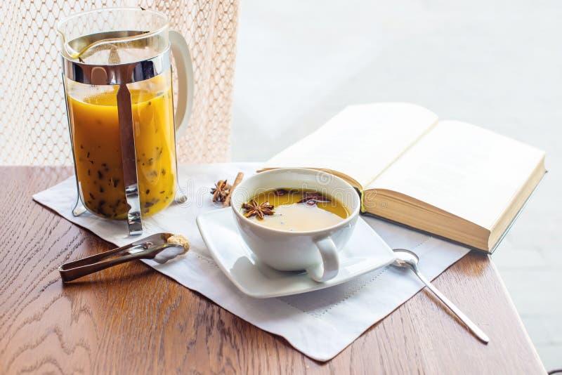 Kopp- och exponeringsglastekanna med kryddigt fruktte med apelsinen royaltyfria foton