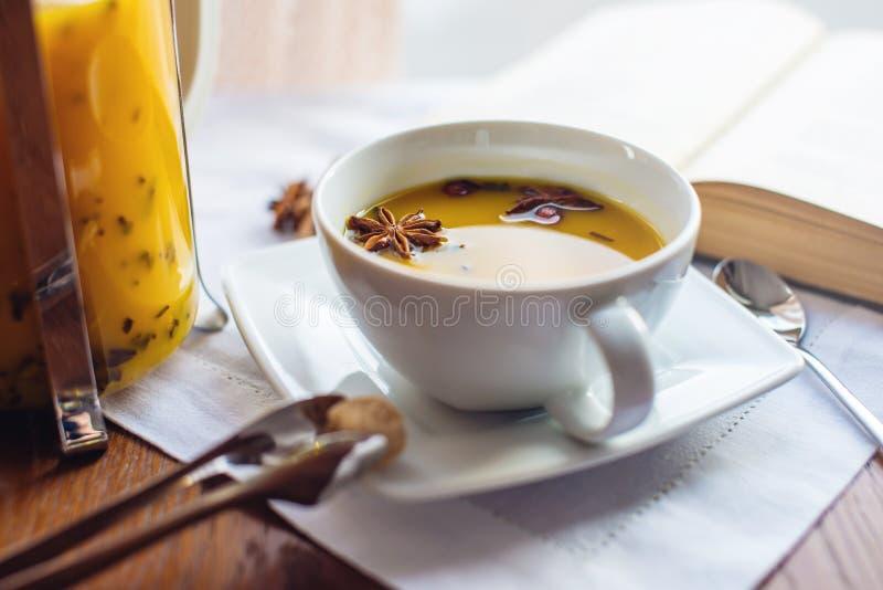 Kopp- och exponeringsglastekanna med kryddigt fruktte med apelsinen arkivbild