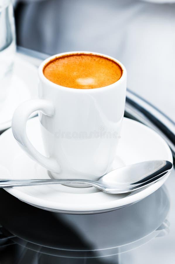 Kopp och tefat för espressokaffe full på nattduksbordcloseupen royaltyfria foton