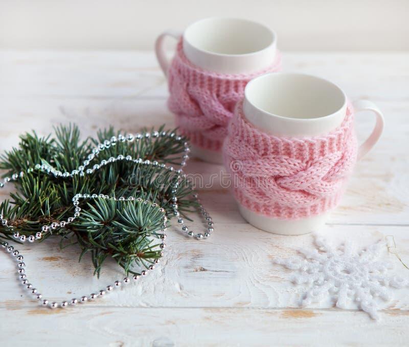 Kopp på den vita trätabellen med den dekorativa dekoren för jul Vinterslags tvåsittssoffabakgrund arkivfoton