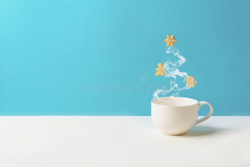 Kopp te eller kaffe med ånga i form för granträd med pepparkakakakor på blå bakgrund Julberömbegrepp kopia arkivfoton