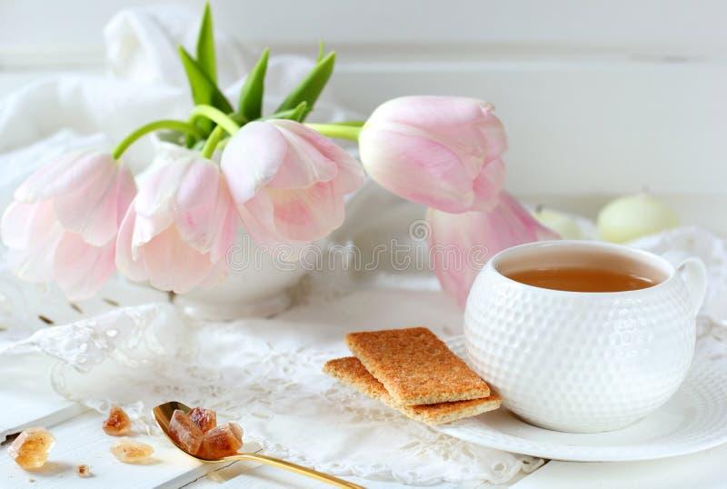 Kopp te, kex och karamellsocker arkivfoto
