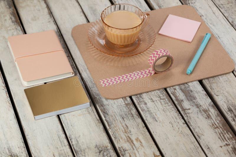 Kopp te, klibbiga anmärkningar, dagbok, notepad, utskrivaven tejp och penna arkivfoto