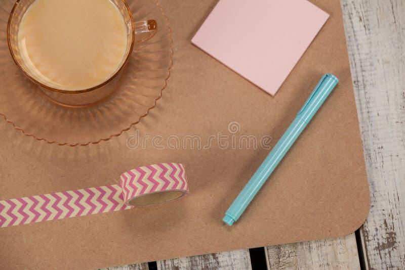 Kopp te, klibbiga anmärkningar, utskrivaven tejp och penna royaltyfri foto