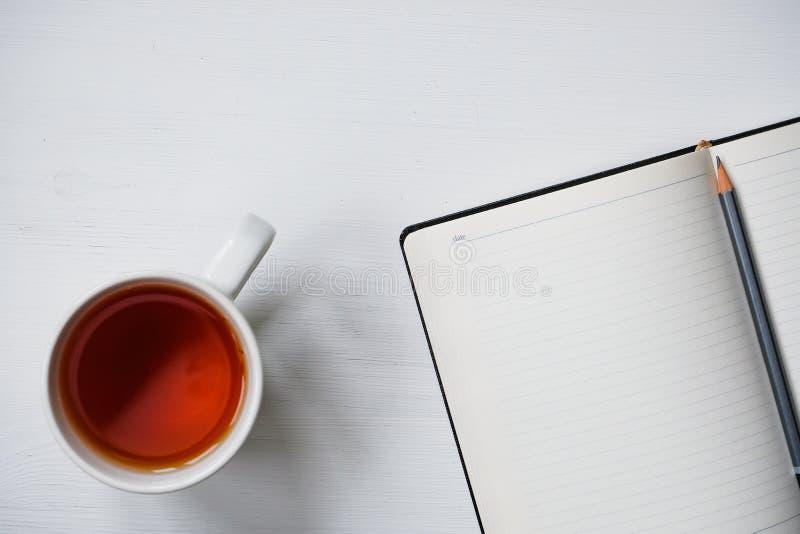 Kopp te med anteckningsboken och blyertspennan p royaltyfria foton