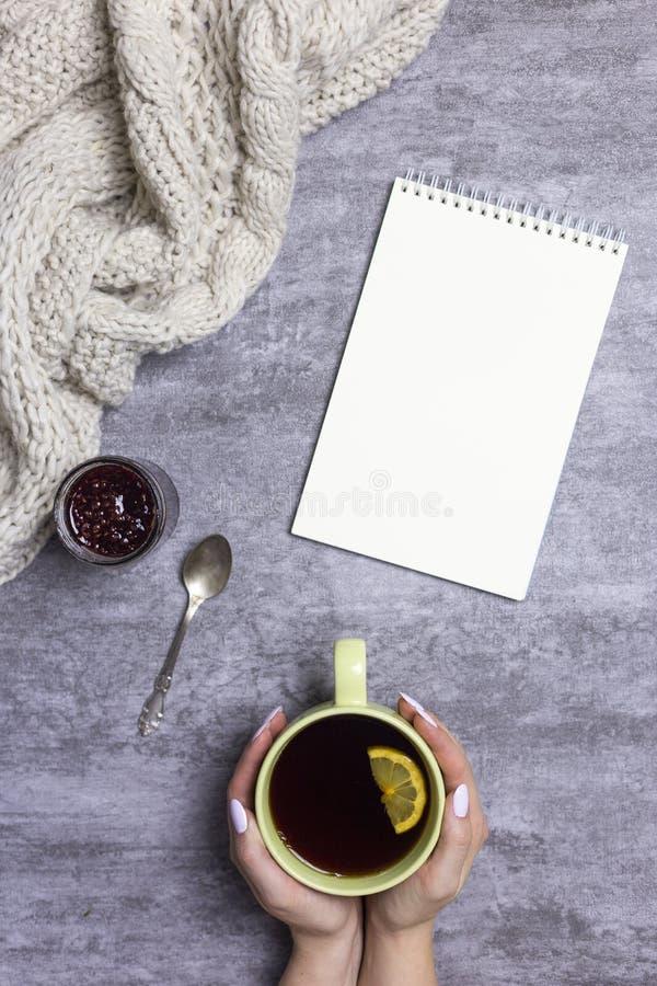 Kopp te med citronen i händer, stucken halsduk, hallondriftstopp, sked och notepad nära, på grå bakgrund arkivfoton