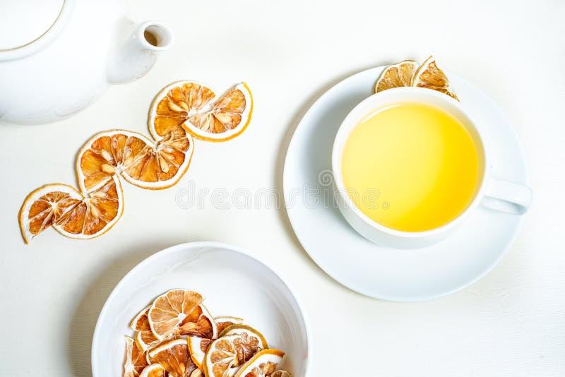 Kopp te med den torkade citronen på sidan och en bunke av den torkade citronen i forcground- och tekrukan och bakgrunden royaltyfri fotografi