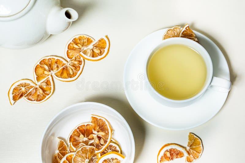 Kopp te med den torkade citronen på sidan och en bunke av den torkade citronen i forcground- och tekrukan och bakgrunden arkivfoton