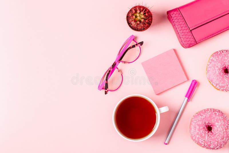 Kopp te med donuts på en rosa pastellfärgad bakgrund arkivbilder