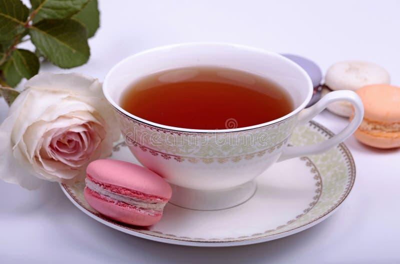 Kopp te med fransk macaron arkivbilder
