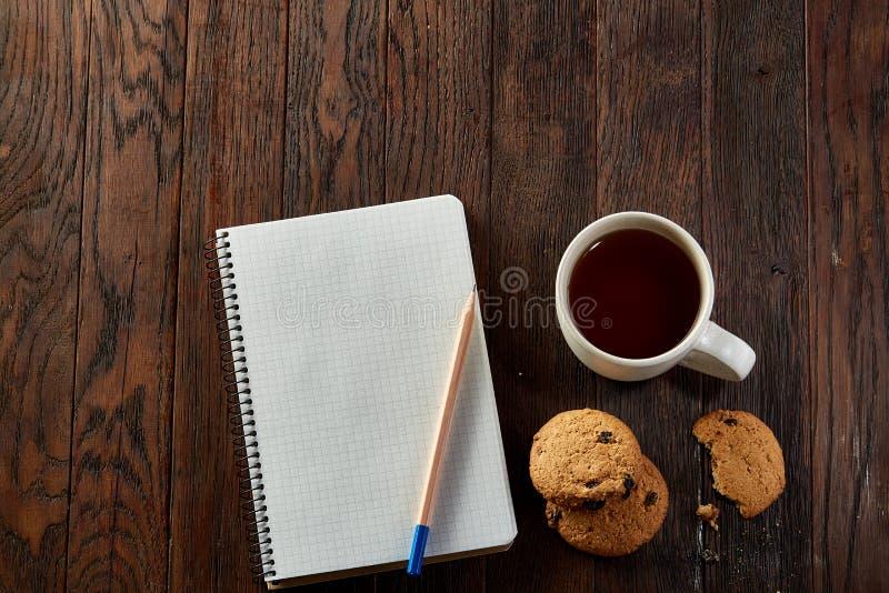 Kopp te med kakor, arbetsboken och en blyertspenna på en träbakgrund, bästa sikt arkivfoton