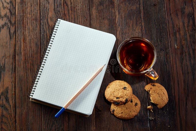Kopp te med kakor, arbetsboken och en blyertspenna på en träbakgrund, bästa sikt royaltyfria foton