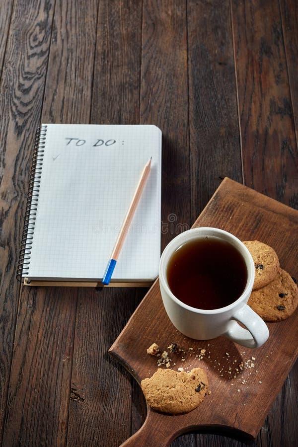 Kopp te med kakor, arbetsboken och en blyertspenna på en träbakgrund, bästa sikt royaltyfri bild