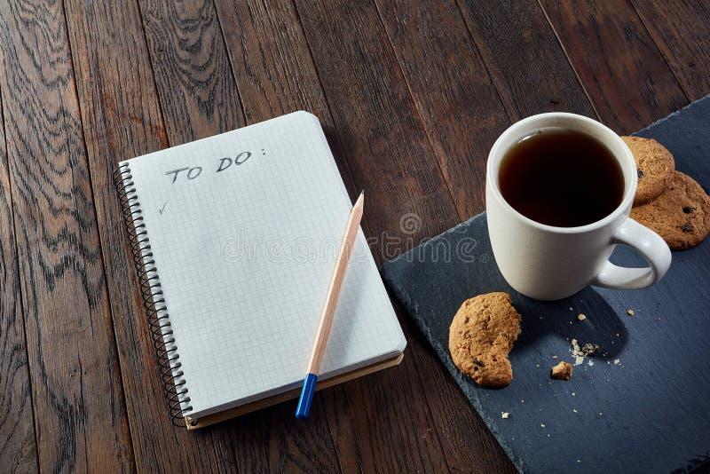 Kopp te med kakor, arbetsboken och en blyertspenna på en träbakgrund, bästa sikt royaltyfri fotografi