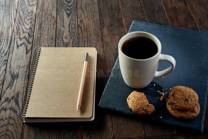 Kopp te med kakor, arbetsboken och en blyertspenna på en träbakgrund, bästa sikt royaltyfria bilder