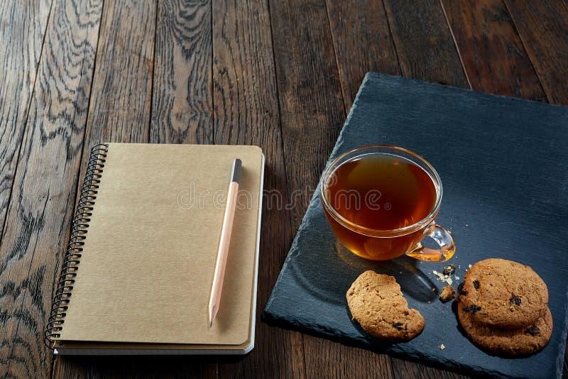Kopp te med kakor, arbetsboken och en blyertspenna på en träbakgrund, bästa sikt royaltyfri foto