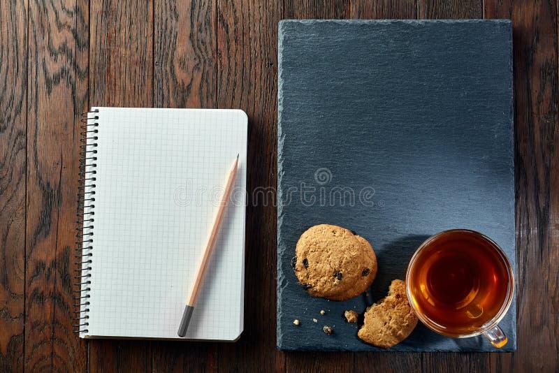 Kopp te med kakor, arbetsboken och en blyertspenna på en träbakgrund, bästa sikt fotografering för bildbyråer