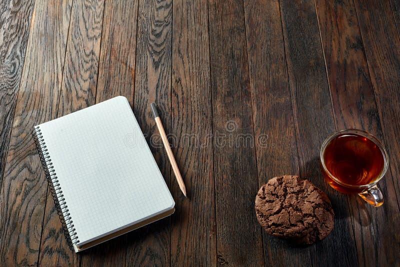 Kopp te med kakor, arbetsboken och en blyertspenna på en träbakgrund, bästa sikt arkivbilder