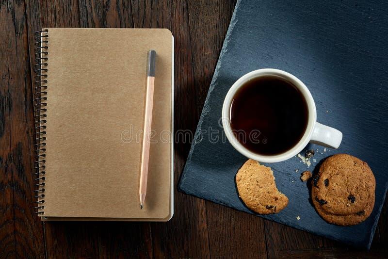 Kopp te med kakor, arbetsboken och en blyertspenna på en träbakgrund, bästa sikt, lodlinje arkivfoto