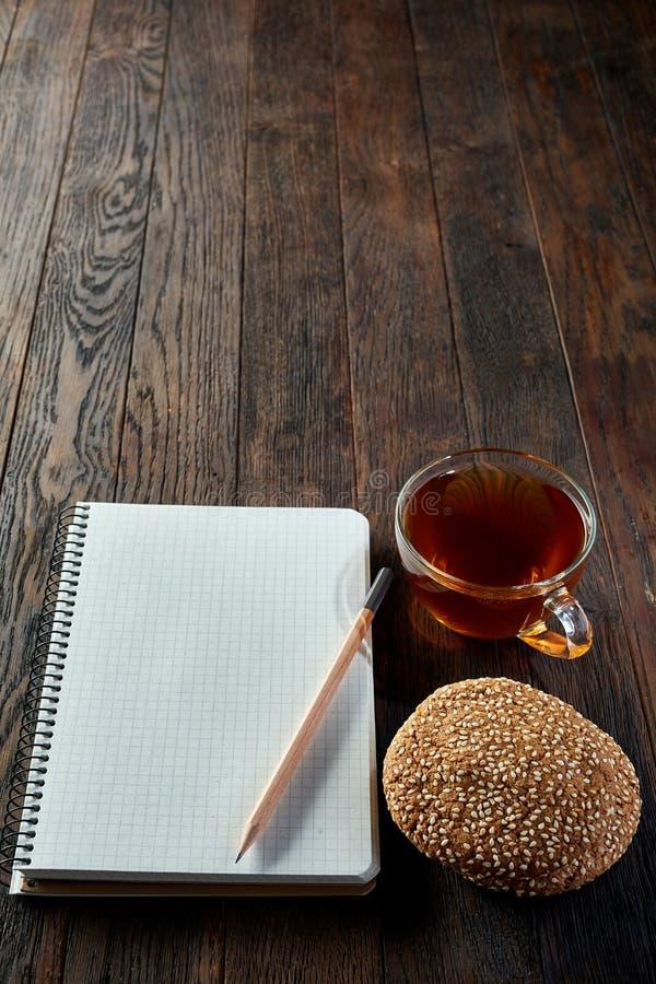 Kopp te med kakor, arbetsboken och en blyertspenna på en träbakgrund, bästa sikt, lodlinje royaltyfria foton