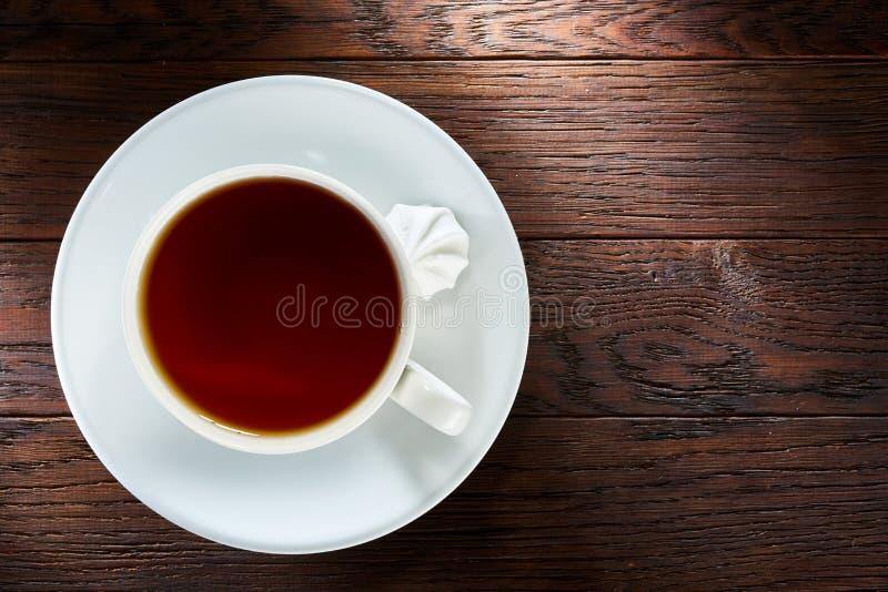 Kopp te med marängar på en träbakgrund, bästa sikt royaltyfri foto