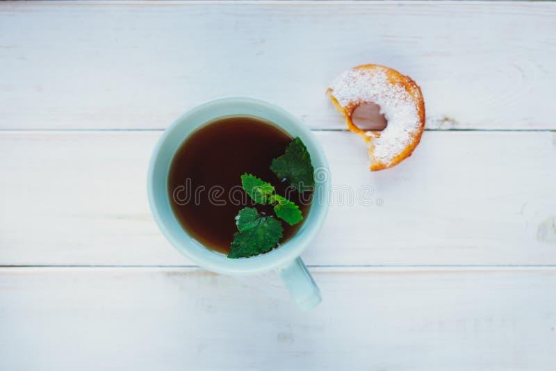 Kopp te med mintkaramellen och munken på en vit bakgrund royaltyfri fotografi