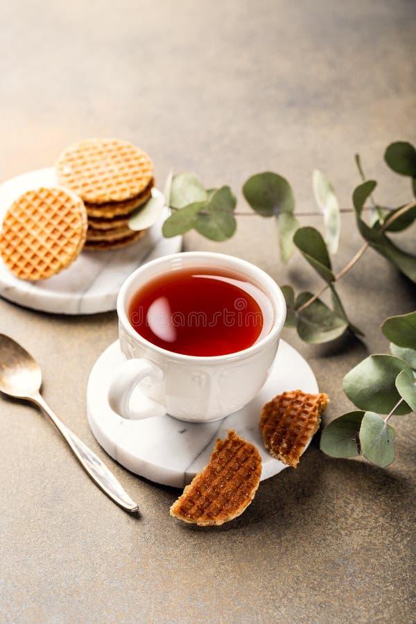 Kopp te med syrupwaffleskakor royaltyfri bild