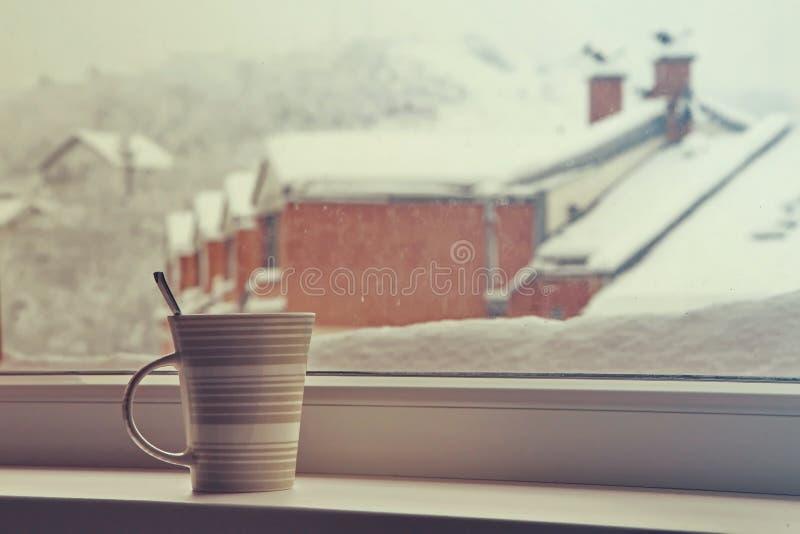 Kopp te nära ett fönster arkivfoto