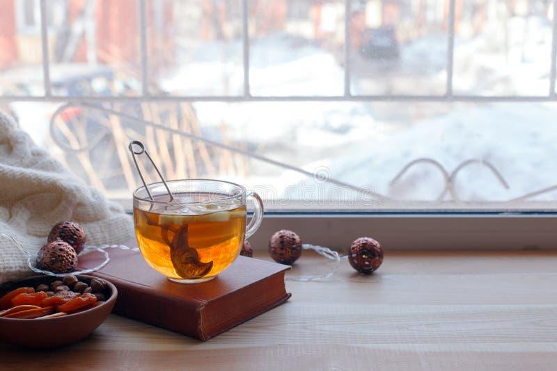 Kopp te och böcker på träfönsterfönsterbrädan Begreppet av läsning, hemtrevlig hem- helg, kopplar av, älskar för att läsa begrepp arkivbilder