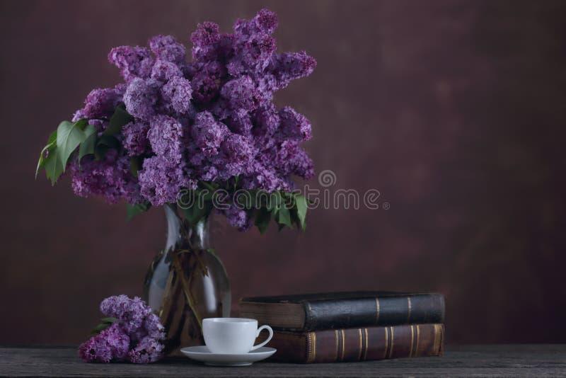 Kopp te och gamla böcker nära boquet av lila blommor royaltyfria bilder