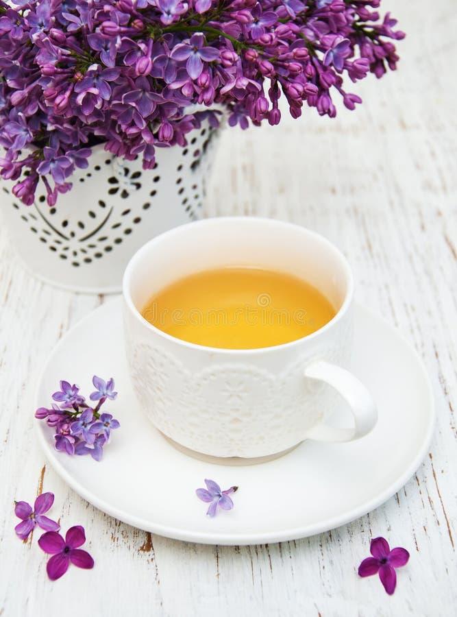 Kopp te- och lilablommor arkivfoto