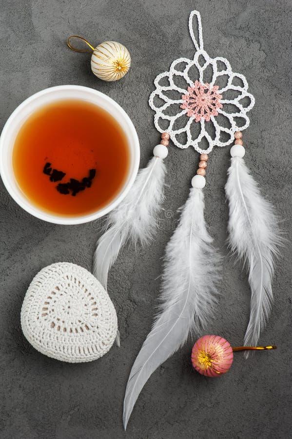 Kopp te och virkad kiselsten arkivfoto