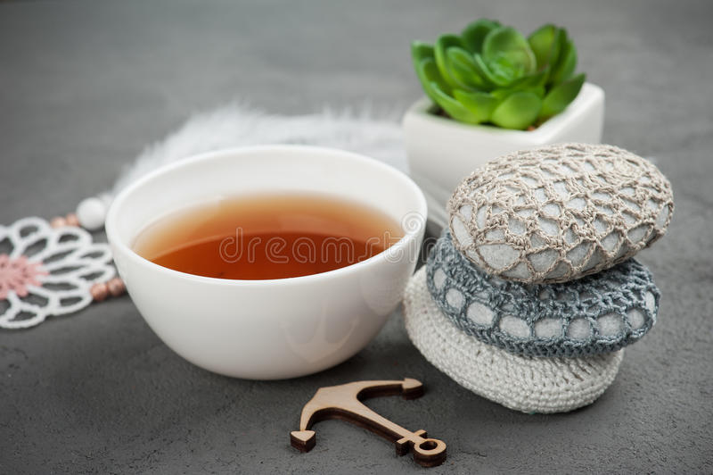 Kopp te och virkade kiselstenar royaltyfri foto
