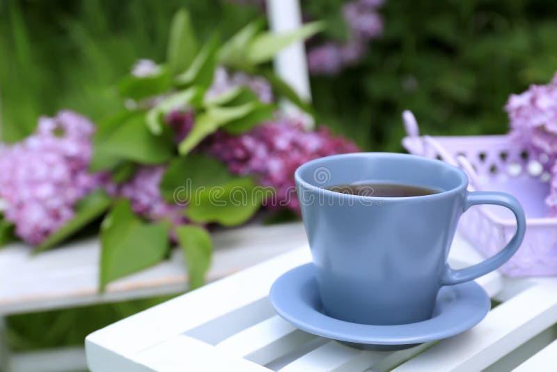 Kopp te på tabell- och lilablommor arkivfoton