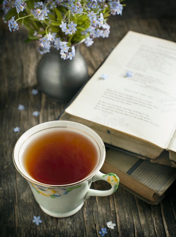 Kopp te, tappningböcker och blåttblommor på tabellen arkivbild