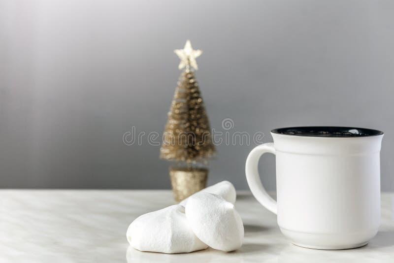 Kopp te, vita marängar och guld- julgran arkivfoto