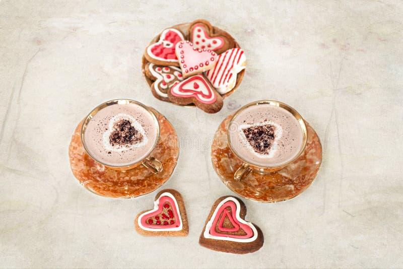 Koppar av cappuccino- och ingefärakex i form av hjärtor royaltyfria bilder