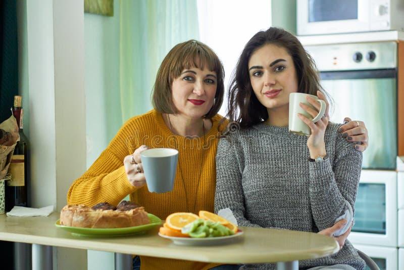 Koppar för mamma- och dotterhållte i det hemtrevliga köket som ser kameran royaltyfri bild
