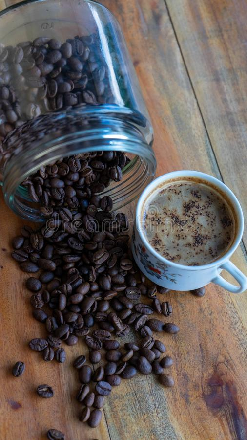 Koppar för vitt kaffe och kaffebönor som spiller omkring med trätabellbakgrunder vektor illustrationer