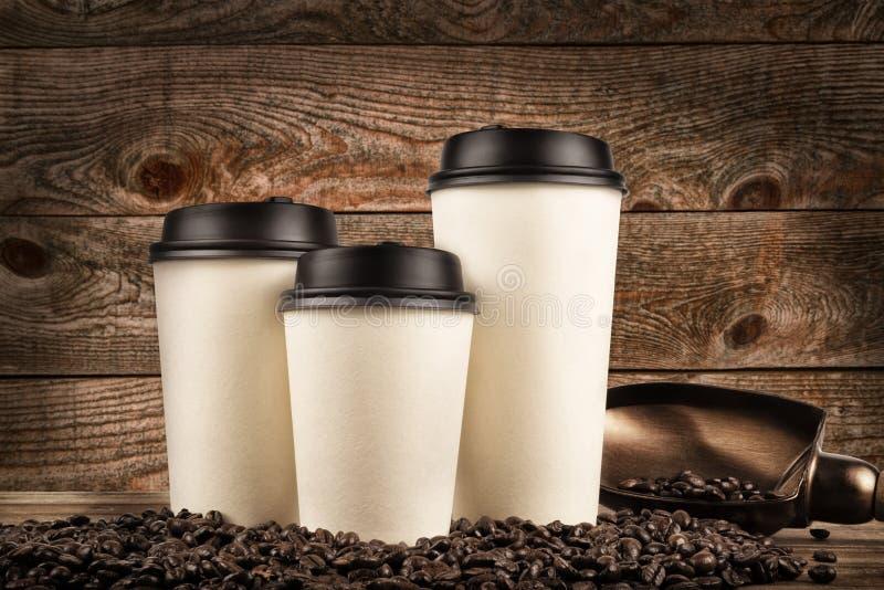Koppar kaffe och kaffebönor på gammal träbakgrund royaltyfria bilder