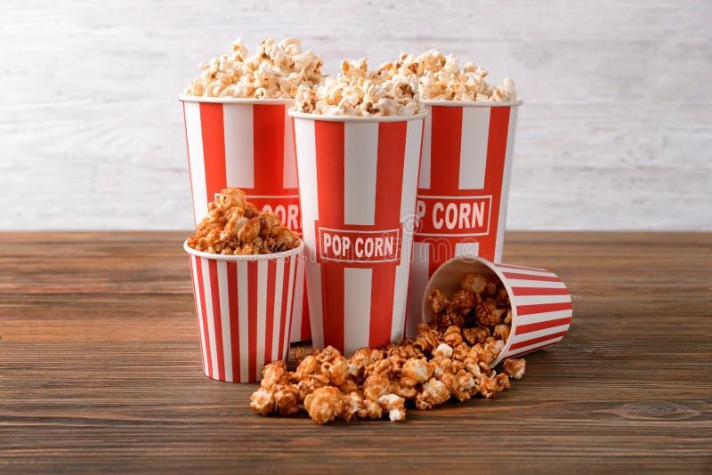 Koppar med smakligt popcorn p? tr?tabellen arkivbild